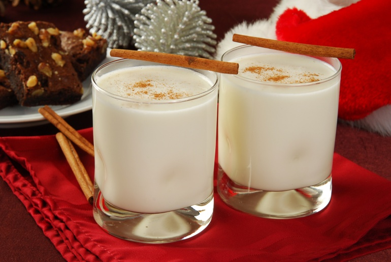 Two glasses of eggnog with brownies and a Santa hat in the background